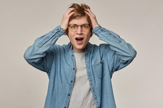 Ritratto di maschio adulto stressato con capelli biondi. indossa una camicia di jeans e occhiali, ha le parentesi graffe. tenendosi per mano sulla testa, frustrato.