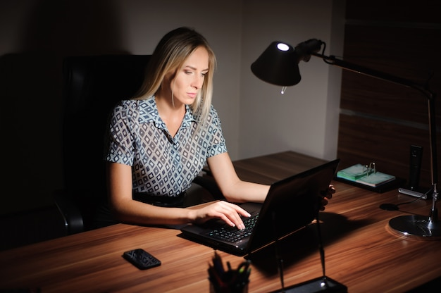 Portrait of stressed businesswoman sitting at office desk