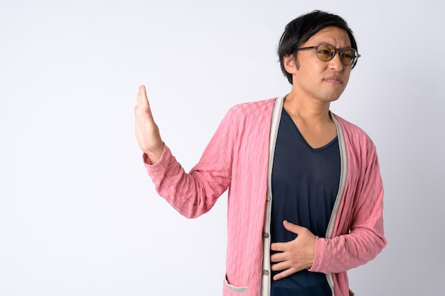 Portrait of stressed japanese man showing stop gesture