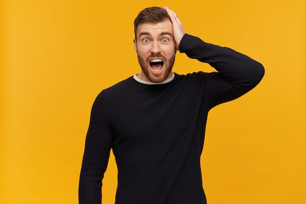 Portrait of stressed male with brunette hair and beard. has piercing. wearing black sweater. puts hand on his head. forgot something. watching shocked , isolated over yellow wall