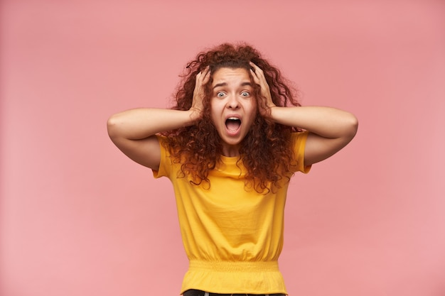 Ritratto di ragazza stressata e rossa con i capelli ricci che indossa la maglietta gialla
