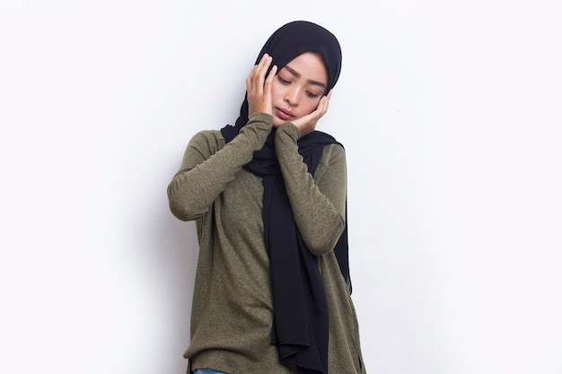 Portrait of stressed sick asian muslim woman with headache on white background