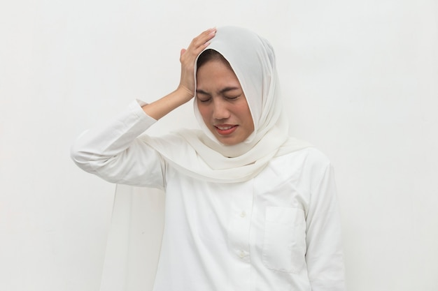 Portrait of stressed sick muslim woman with headache ill woman suffers from vertigo dizziness migraine hangover health care concept young adult asian woman model