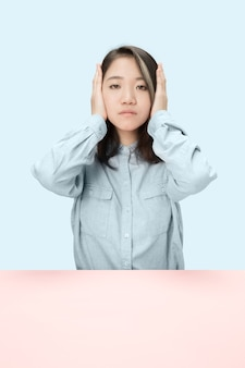 Portrait of stressed woman sitting with eyes closed and covering with hands. isolated on blue studio background. i can not hear anything