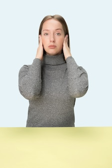 Portrait of stressed woman sitting with eyes closed and covering with hands. isolated on blue studio background.
