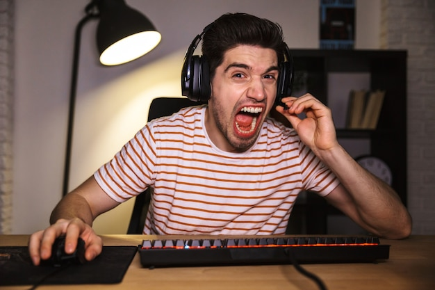 Portrait of stressed young man 20s wearing headset yelling, while sitting at desk in room and looking at computer monitor