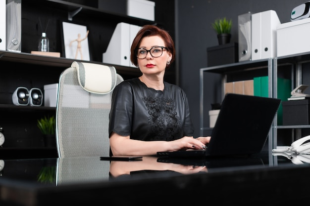 Portrait of strict businesswoman with laptop in stylish office