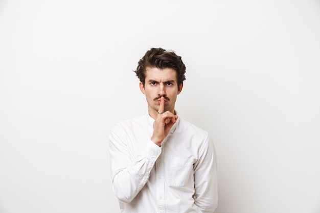 Portrait of strict mustached man wearing shirt holding finger at his lips isolated on white