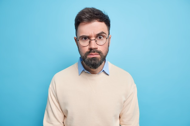 Portrait of strict serious man looks angrily at you being dissatisfied with something demands explanations wears round spectacles and casual sweater