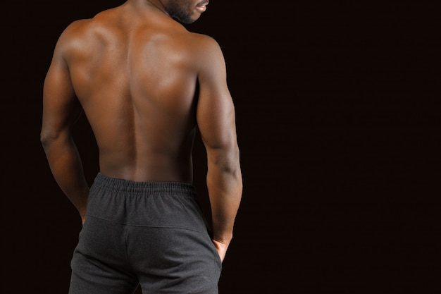 Portrait of a strong afro-american man showing off his physique on black