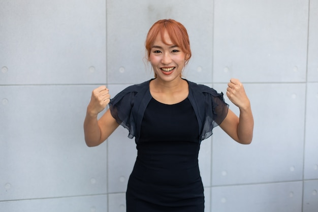 Portrait strong asian woman flexing both arms muscles. success winning concept.