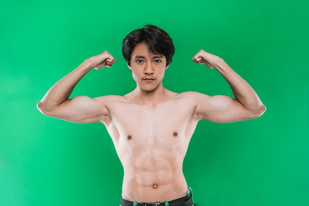 Portrait strong athletic man showing muscular body over, on green wall