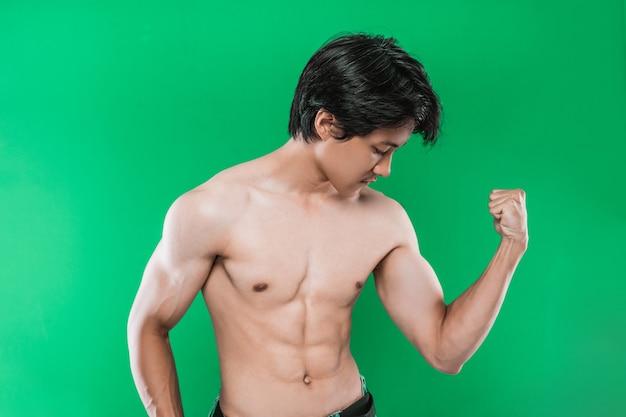 Портрет сильного спортивного человека, показывающего мускулистое тело на зеленой стене