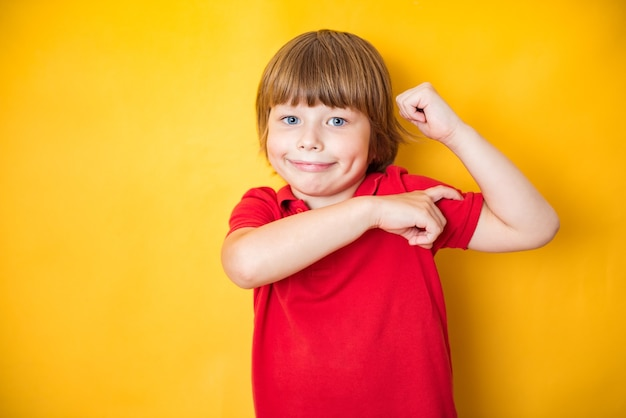Portrait of a strong boy showing the muscles of his arms on yellow background