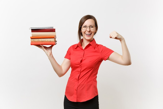 Portrait of strong business teacher woman in red shirt showing biceps muscles, holding stack text books in hands isolated on white background. education or teaching in high school university concept.