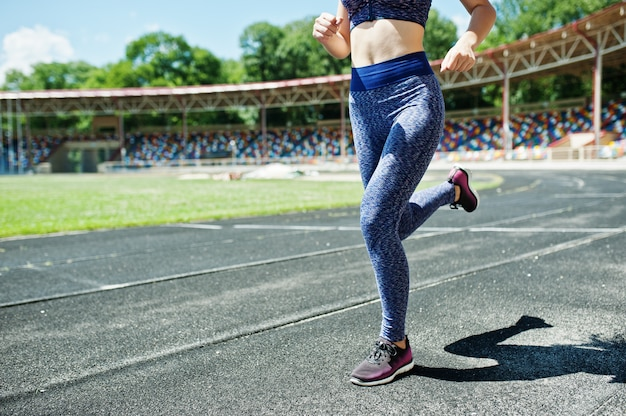 Portrait of a strong fit girl in sportswear running in the stadium.