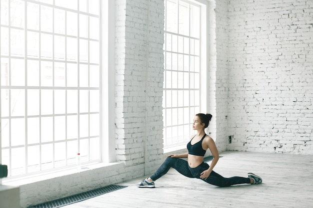 Portrait of strong flexible young caucasian sportswoman in trendy sports outfit doing stretching pose, preparing for front splits. attractive fit girl doing exercises to strengthen pelvic health