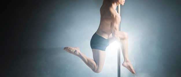 Portrait of strong male model performing a pole dance
