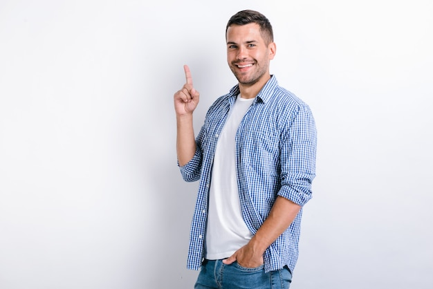 Portrait of strong man in standing, looking at camera with toothy smile and pointing at empty place at the white background. indoor studio shot