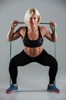 Portrait of strong sports woman doing sit-ups while stretching with elastic rubber