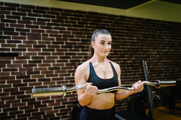 Portrait of strong sporty woman is exercising with barbell in gym