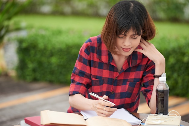 Portrait of student busy with homework in campus outdoors