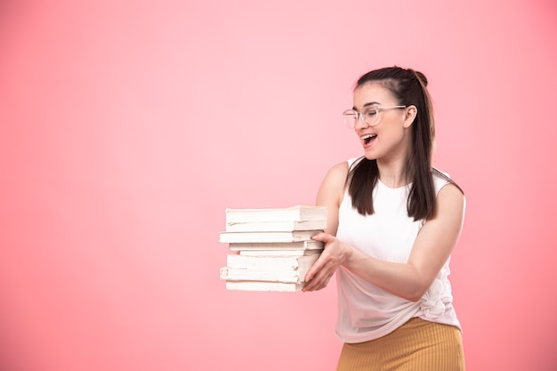 Portrait of a student girl with glasses on a pink background posing with books in her hands. concept of education and hobbies.