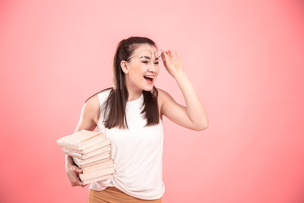 Portrait of a student girl with glasses on a pink background with books in her hands. concept of education and hobbies.