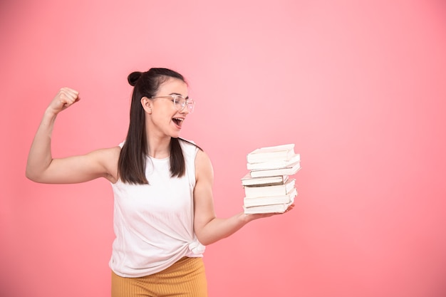 Portrait of a student girl with glasses posing with books in her hands. concept of education and hobbies.