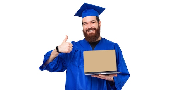 Portrait of student man in blue robe showing thumb up and laptop with blank screen
