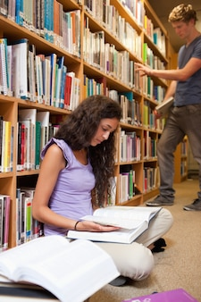 Portrait of a student reading a book while her classmate is choo