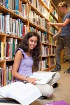 Portrait of a student with a book while her classmate is choosin