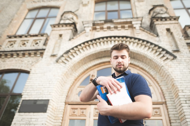 Portrait of a student with books in his hands against the background of a building of the old university.