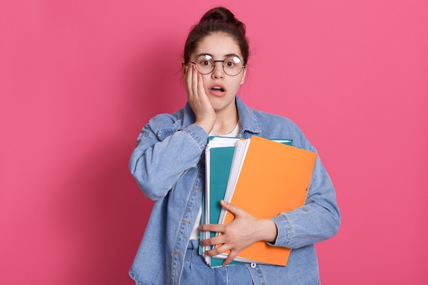 Portrait of student with hair bun, wears denim and rounded glasses, holding colored paper folders