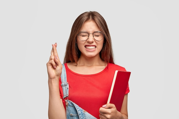 Portrait of student with long hair keeps fingers crossed for good luck on exam, holds textbook