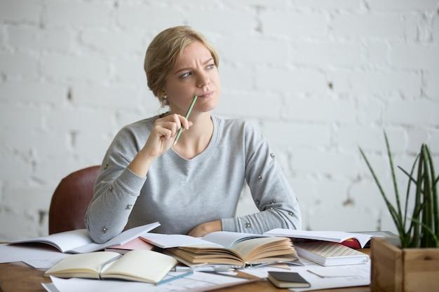 Ritratto di una donna studente alla scrivania, aggrottò la fronte