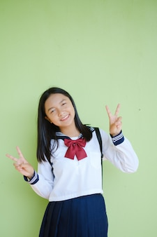 Portrait student young girl in uniform school and backpack on green wall.  asian girl teenager