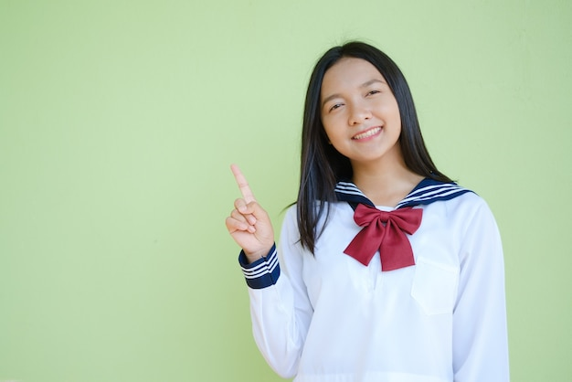 Portrait student young girl in uniform school on green wall.  asian girl teenager