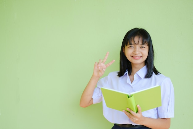 Portrait student young girl in uniform school with green book on green wall.  asian girl teenager