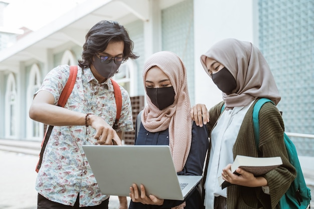 Portrait of students wearing masks discussing together with laptop on the campus yard.