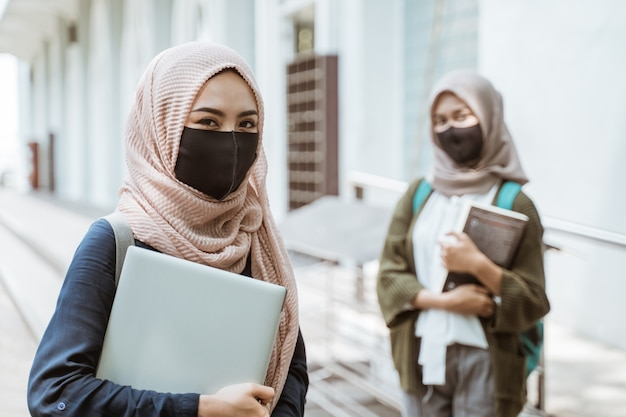 Portrait of students wearing masks looking at the front on the campus yard with friends in the background.