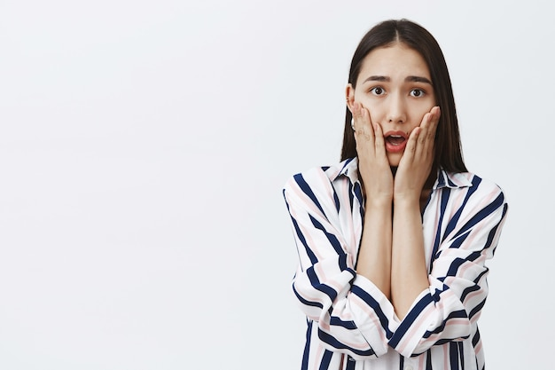 Portrait of stunned and intense good-looking female student in striped blouse, gasping, holding palms on cheeks while sympathizing heartbreaking story, posing over gray wall