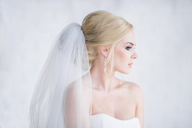 Portrait of stunning blonde bride in dress with naked shoulders