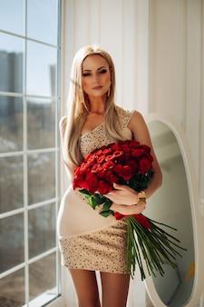 Ritratto di splendida modella bionda caucasica in mini abito beige con elementi scintillanti che tengono bouquet di rose rosse in piedi vicino alla finestra alla luce del sole.