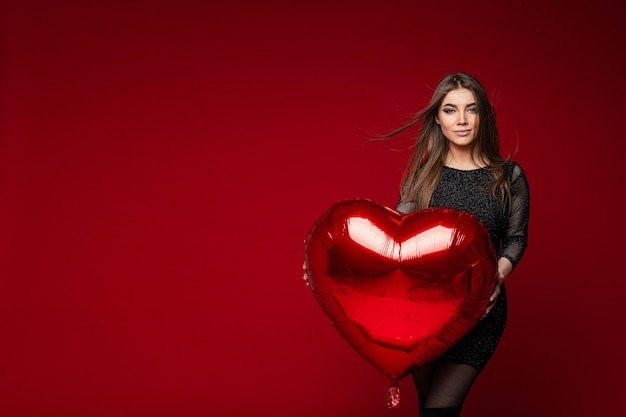 Portrait of stunning brunette girl in dark cocktail dress with red heart balloon on red background. saint valentines day concept.