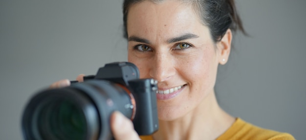 Portrait of stunning brunette photographer on grey isolated background