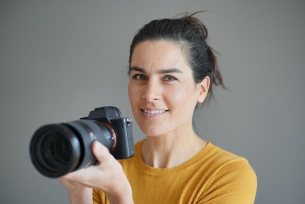 Portrait of stunning brunette photographer on grey