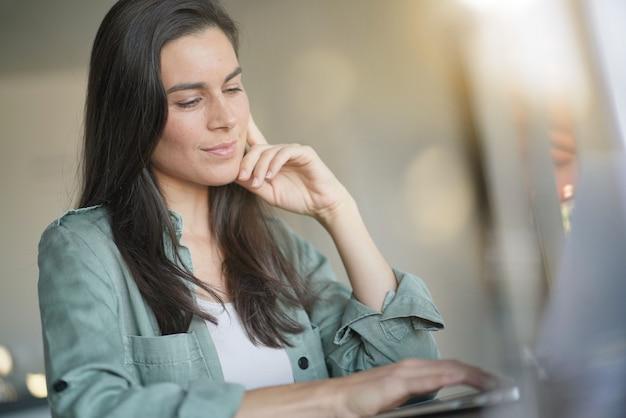Portrait of stunning brunette smiling at her laptop