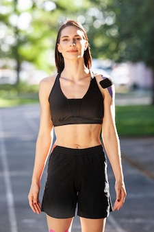 Portrait of stunning muscular brunette woman wearing black sports outfit posing outdoors. young athlete standing with hands on waist at stadium, colorful treatment on body, kinesiotaping.
