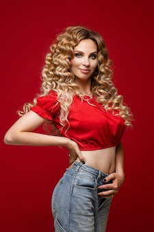 Portrait of stunning slender woman with long wavy hair in red crop top and jeans posing on bright red background, smiling at camera.